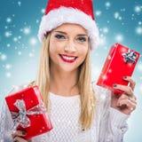 Bella donna con il cappello di Santa, tenente il contenitore di regalo rosso due - precipitazioni nevose Immagini Stock Libere da Diritti