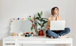 Bella donna con il computer portatile che si siede su una tavola fotografie stock