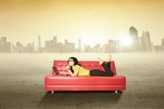 Bella donna con il computer portatile sul sofà all'aperto Immagine Stock Libera da Diritti
