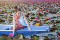 Bella donna con il fiore di loto al mare rosso del loto Fotografie Stock Libere da Diritti