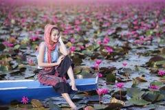 Bella donna con il fiore di loto al mare rosso del loto Fotografia Stock