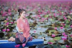 Bella donna con il fiore di loto al mare rosso del loto Immagine Stock