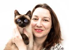 Bella donna con il gatto siamese nel suo sorriso di armi al Ca Fotografie Stock Libere da Diritti