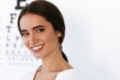 Bella donna con il grafico di prova dell'occhio all'ufficio di oftalmologia fotografia stock libera da diritti
