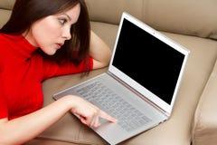 Bella donna con il pollice della tastiera sul libro ultra. Fotografia Stock