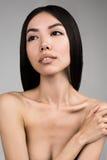 Bella donna con il ritratto perfetto della pelle isolato su Gray Background Fotografia Stock