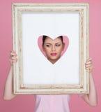 Bella donna con il suo fronte incorniciato da un cuore Fotografia Stock