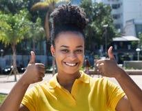Bella donna con l'acconciatura stupefacente che mostra entrambi i pollici su Fotografia Stock Libera da Diritti