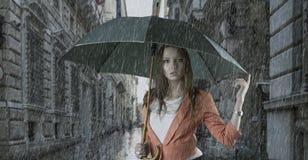 Bella donna con l'ombrello in città sotto pioggia fotografia stock