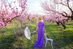 Bella donna con l'ombrello un giorno soleggiato nel giardino sbocciante, il giorno di molla adorabile per una passeggiata, il fio immagini stock