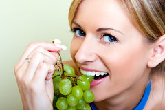 Bella donna con l'uva verde Fotografia Stock