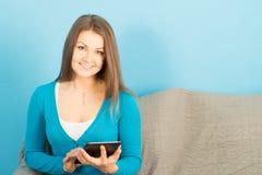 Bella donna con la compressa ed il telefono a casa Fotografie Stock Libere da Diritti