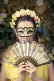 Bella donna con la corona, la maschera ed il fan floreali immagine stock