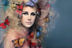 Bella donna con la farfalla in grandi capelli ricci. Fotografia Stock