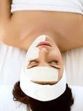 Bella donna con la maschera cosmetica sul fronte. La ragazza ottiene il trattamento Fotografia Stock Libera da Diritti
