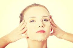 Bella donna con la maschera del collagene sul fronte Immagini Stock