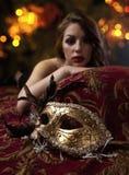 Bella donna con la maschera di carnevale dell'oro, fuoco su una priorità alta Fotografia Stock