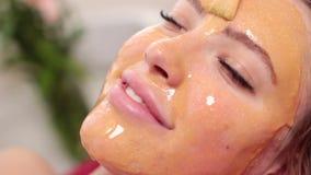 Bella donna con la maschera facciale al salone di bellezza archivi video