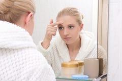 Bella donna con la pelle di problema che esamina specchio in bagno Fotografie Stock