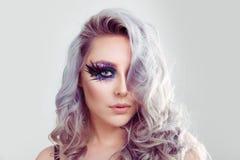 Bella donna con la piuma porpora artistica di trucco degli occhi azzurri sui cigli e sui capelli ricci fotografie stock