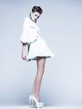 Bella donna con le gambe lunghe in vestito, pelliccia bianca e tacchi alti posanti nello studio Immagini Stock Libere da Diritti