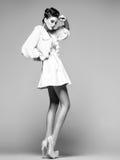 Bella donna con le gambe lunghe in vestito, pelliccia bianca e tacchi alti posanti nello studio Fotografia Stock