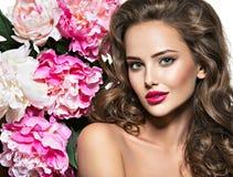 Bella donna con le labbra ed il fiore rossi luminosi vicino al fronte Immagini Stock Libere da Diritti