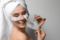 Bella donna con le maschere del fronte e di occhio del cotone fotografia stock