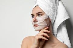 Bella donna con le maschere del fronte e di occhio del cotone contro fondo leggero fotografia stock