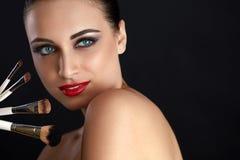 Bella donna con le spazzole di trucco Trucco Immagini Stock