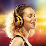 Bella donna con musica d'ascolto delle cuffie Immagine Stock