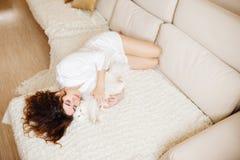 Bella donna con peli ricci in una vestaglia di seta bianca nelle prime ore del mattino che gioca con il gatto lanuginoso bianco c Fotografia Stock