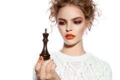 Bella donna con trucco di sera che tiene un pezzo degli scacchi di re Fotografie Stock