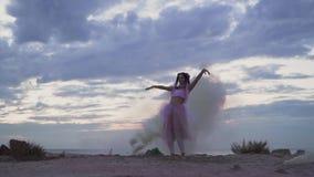 Bella donna con trucco scintillante in vestito rosa che balla nella foschia dalle bombe fumogene all'aperto Il ballo della a video d archivio