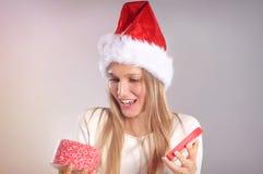 Bella donna con un cappello di Santa che apre un contenitore di regalo Fotografia Stock