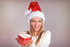 Bella donna con un cappello di Santa che tiene un contenitore di regalo Fotografie Stock Libere da Diritti