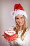 Bella donna con un cappello di Santa che tiene un contenitore di regalo Fotografia Stock Libera da Diritti
