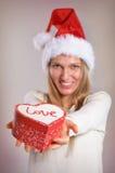 Bella donna con un cappello di Santa che tiene un contenitore di regalo Fotografie Stock
