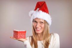 Bella donna con un cappello di Santa che tiene un contenitore di regalo Fotografia Stock