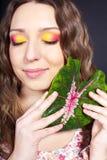 Bella donna con un fiore in sua mano Fotografie Stock Libere da Diritti