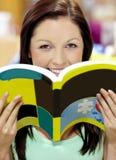 Bella donna con un libro che sorride in una libreria Fotografia Stock Libera da Diritti