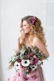 Bella donna con un mazzo dei fiori in un vestito rosa Fotografia Stock