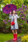 Bella donna con un ombrello in stivali di gomma rossi Fotografia Stock Libera da Diritti