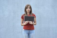Bella donna con un segno sui precedenti di un muro di cemento immagine stock
