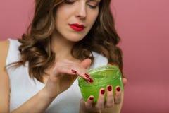 Bella donna con una bottiglia del gel di vera dell'aloe Fotografia Stock