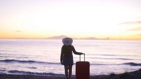 Bella donna con una valigia sulla spiaggia soleggiata video d archivio