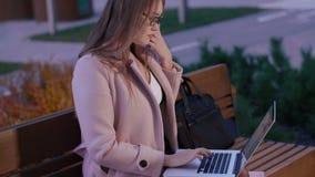 Bella donna concentrata che scrive sul computer portatile e che fa lavoro a distanza in parco video d archivio