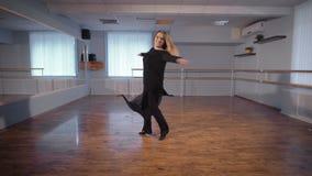 Bella donna dai capelli bianchi nel dancing nero di seta del vestito nell'aula con la sbarra e lo specchio di balletto sulle pare archivi video