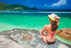 Bella donna dai capelli lunghi in bikini che si rilassa sulle rocce sopra il mare Mahe Islan, Seychelles Immagini Stock