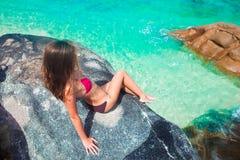 Bella donna dai capelli lunghi in bikini che si rilassa sulle rocce sopra il mare Mahe Islan, Seychelles Immagini Stock Libere da Diritti